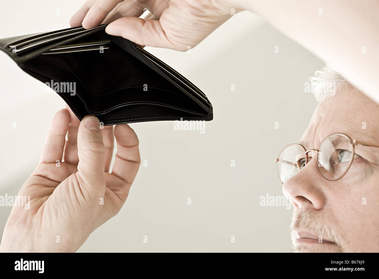 A man looking in an empty wallet Stock Photo