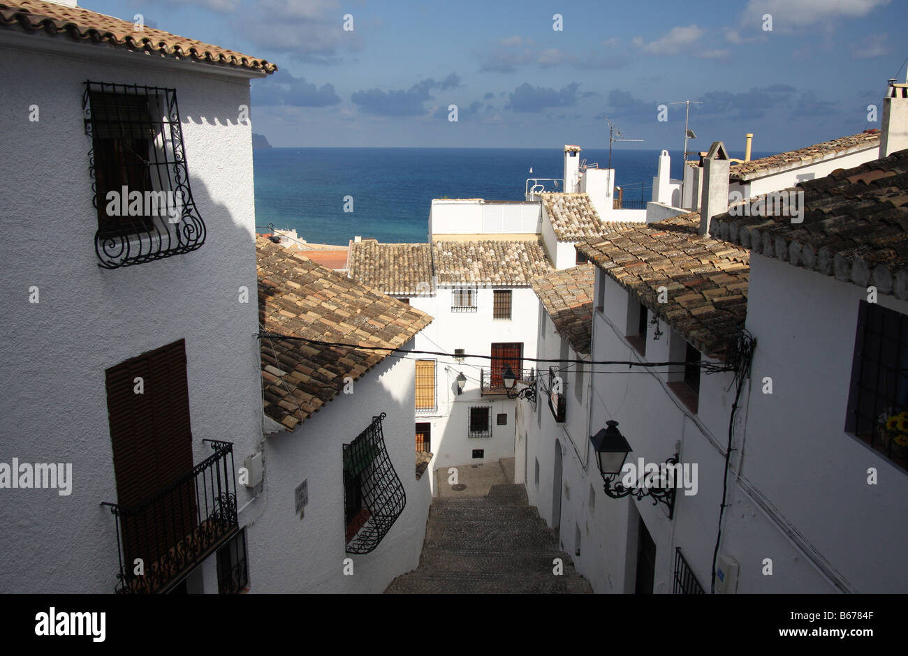 Whitewashed house-fronts and tiled roofs looking out onto the Mediterranean sea in Altea, Spain - Stock Image