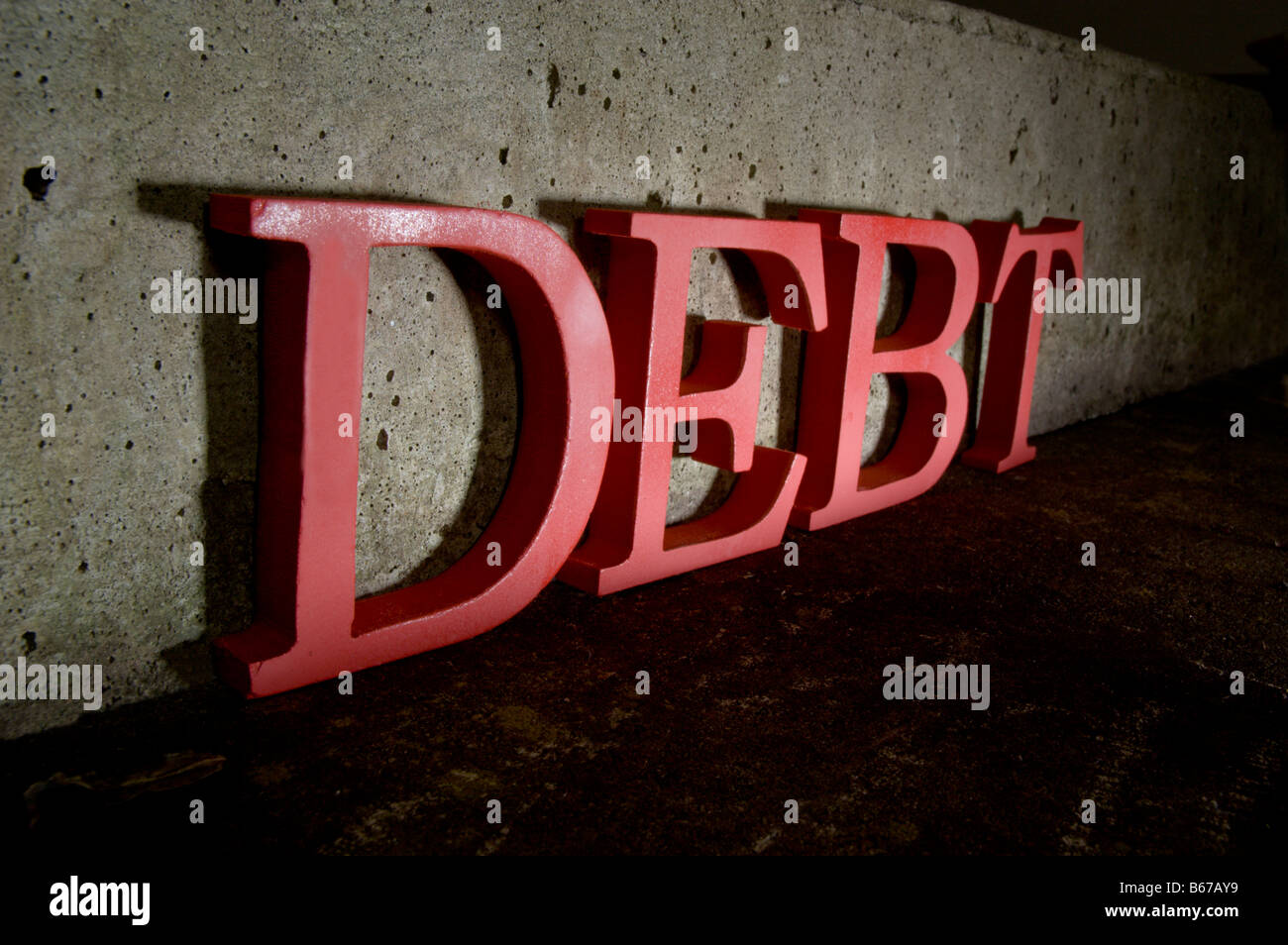 The word debt in red against cold concrete - Stock Image