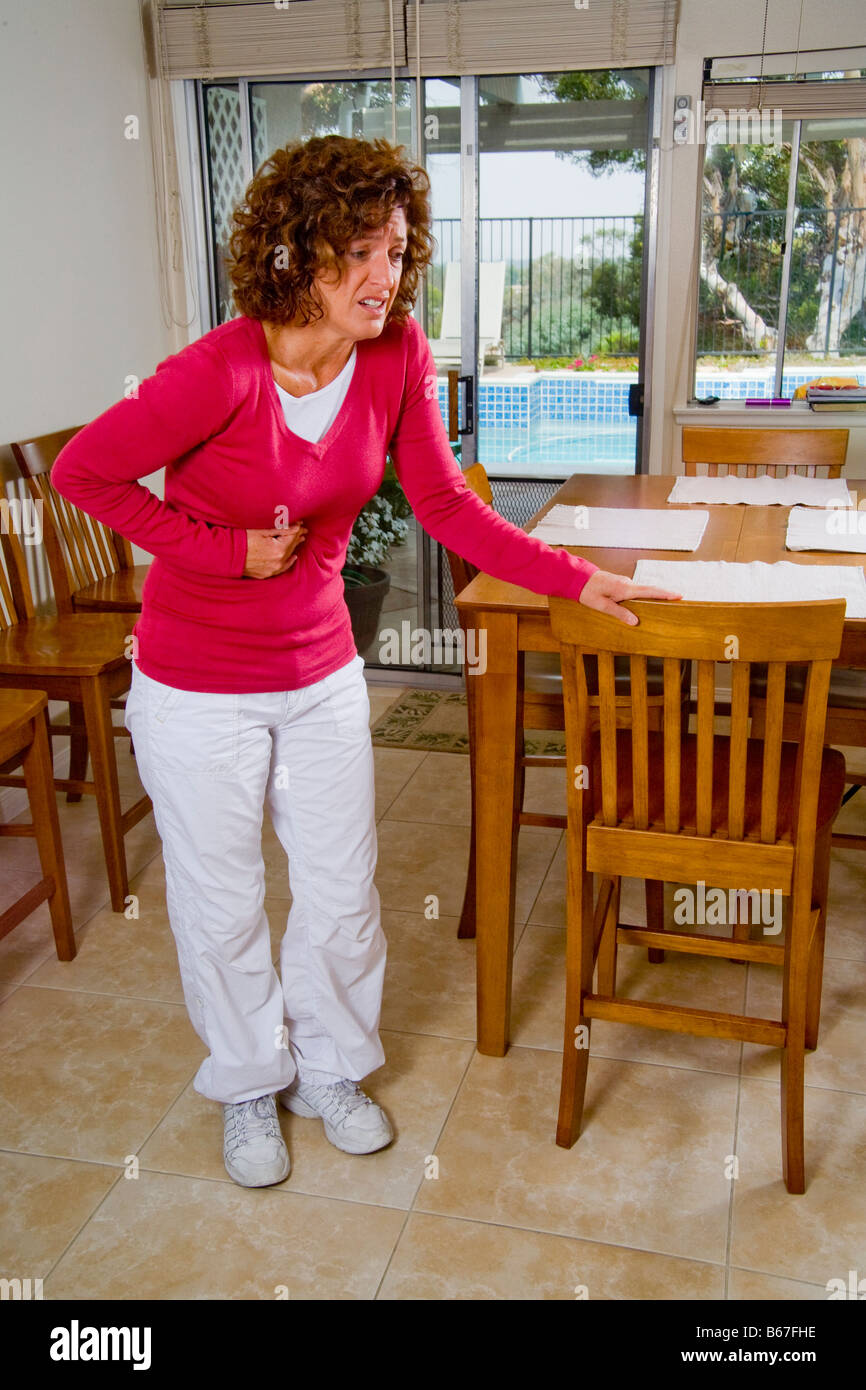 Woman bent over in kitchen stock photos woman bent over in kitchen a hypocondriac winces in imagined pain in her kitchen in mission viejo ca stock image workwithnaturefo
