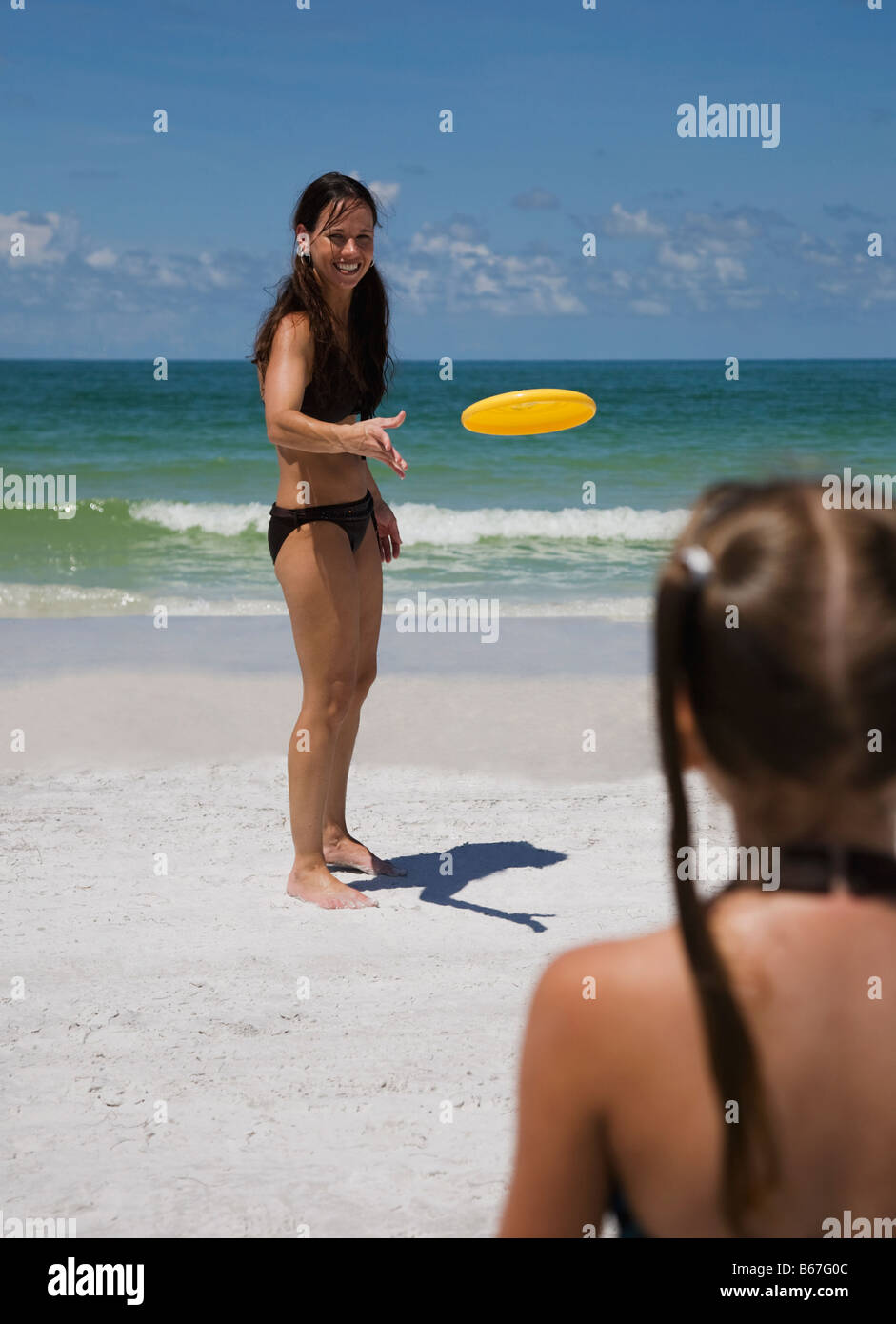 Mother and daughter (5-9) playing frisbee on beach Stock Photo
