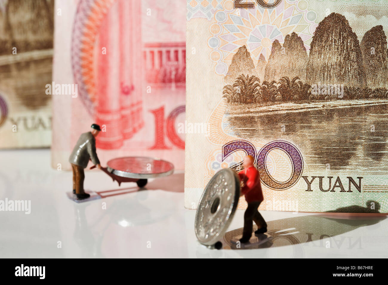 Figurines of manual workers pushing Chinese coins on push carts - Stock Image