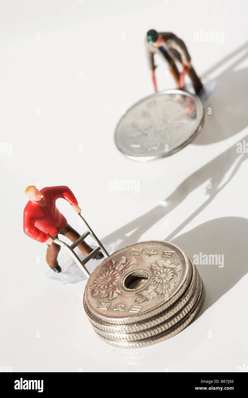 Figurine of manual workers pushing Chinese coins on push cart - Stock Image