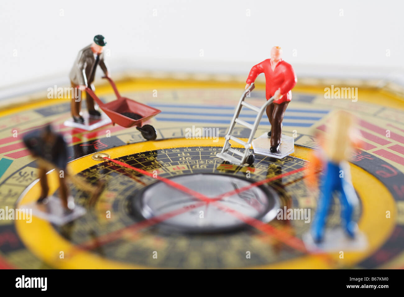 Figurines of manual workers working in feng shui compass - Stock Image