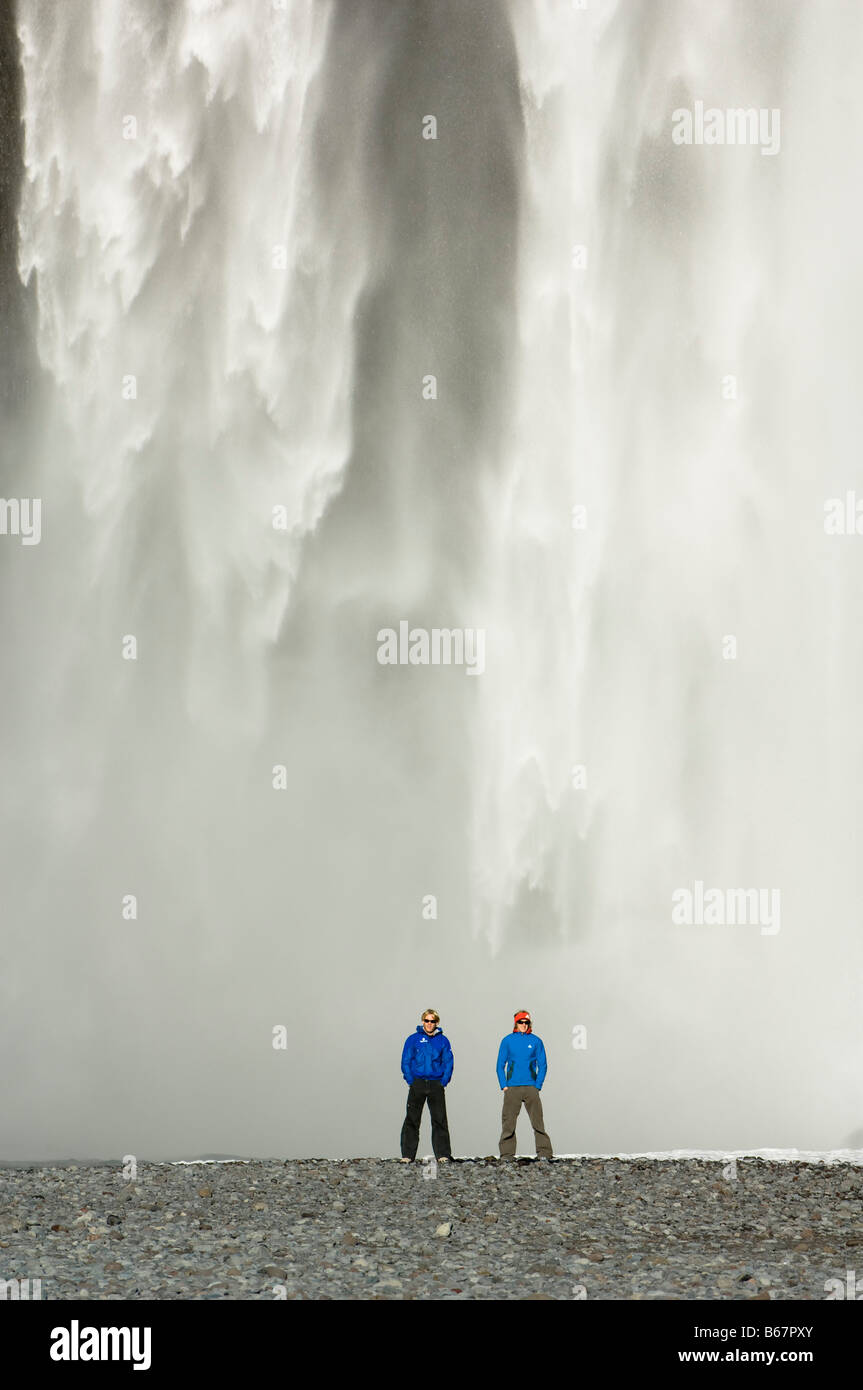 Two men stood in front of a waterfall, Iceland - Stock Image