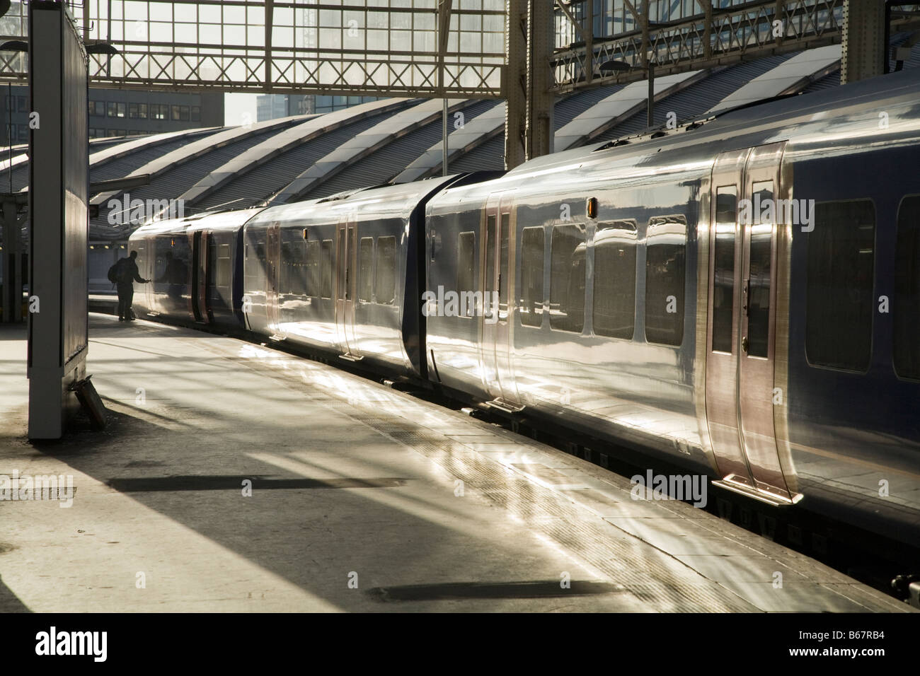 Southwest Trains train and single passenger at the far end of the platform. Waterloo rail station, London. UK. - Stock Image
