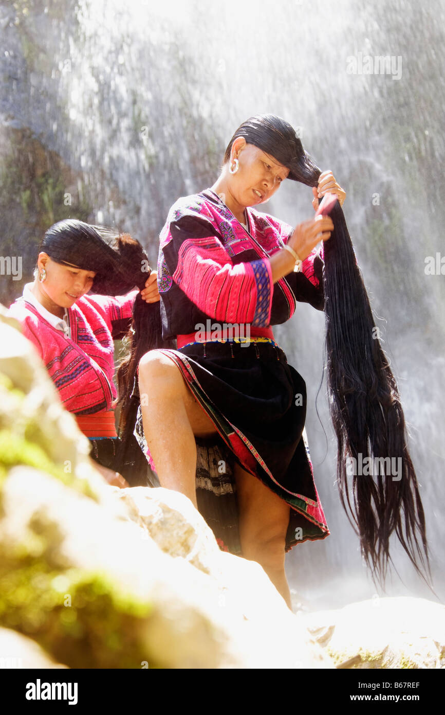 Mature woman and a mid adult woman combing their wet hair, Jinkeng Terraced Field, Guangxi Province, China - Stock Image
