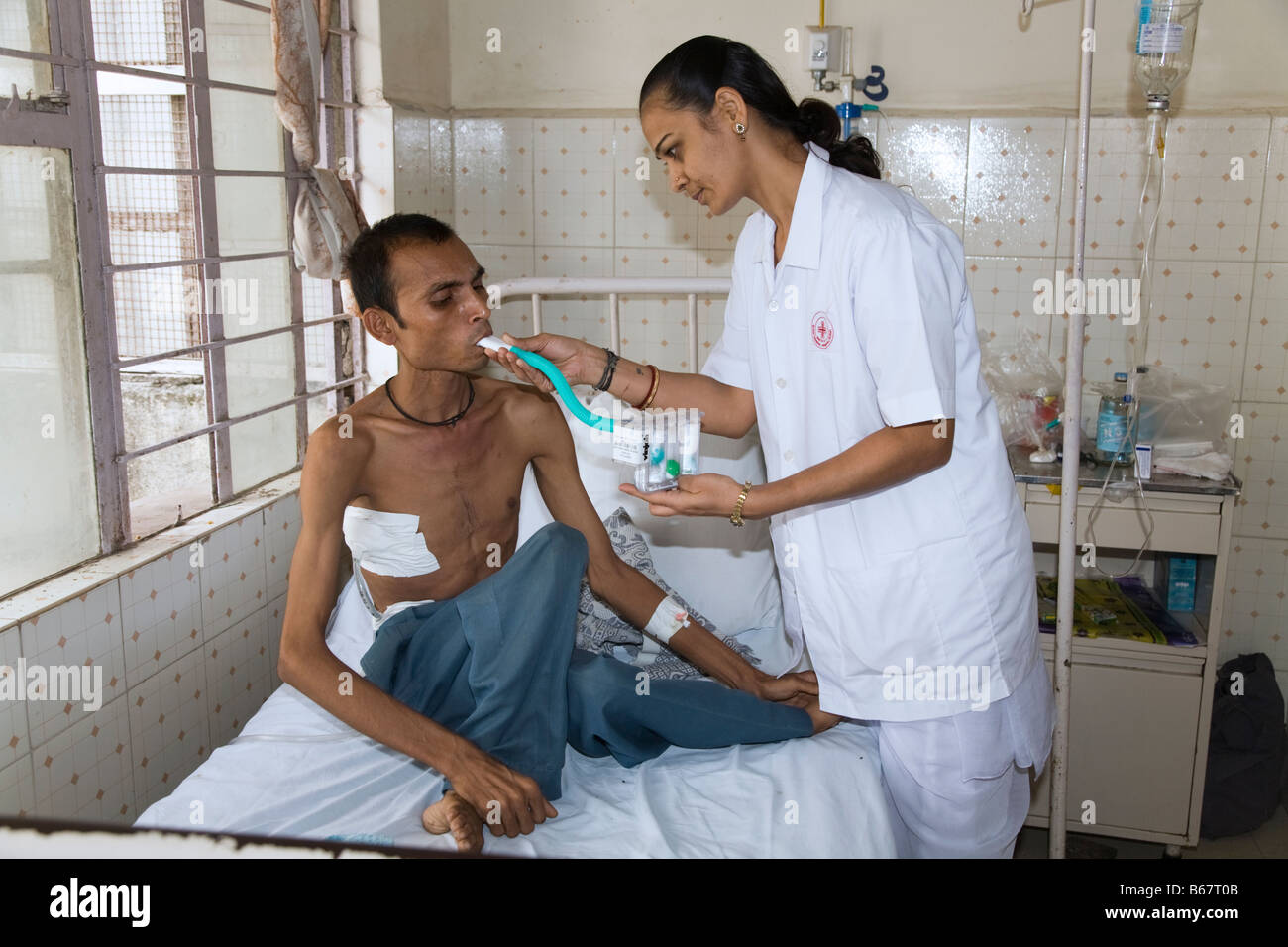 Nurse giving a breathing test to a sick patient on a general ward of the New Civil Hospital, Surat. Gujarat. India - Stock Image