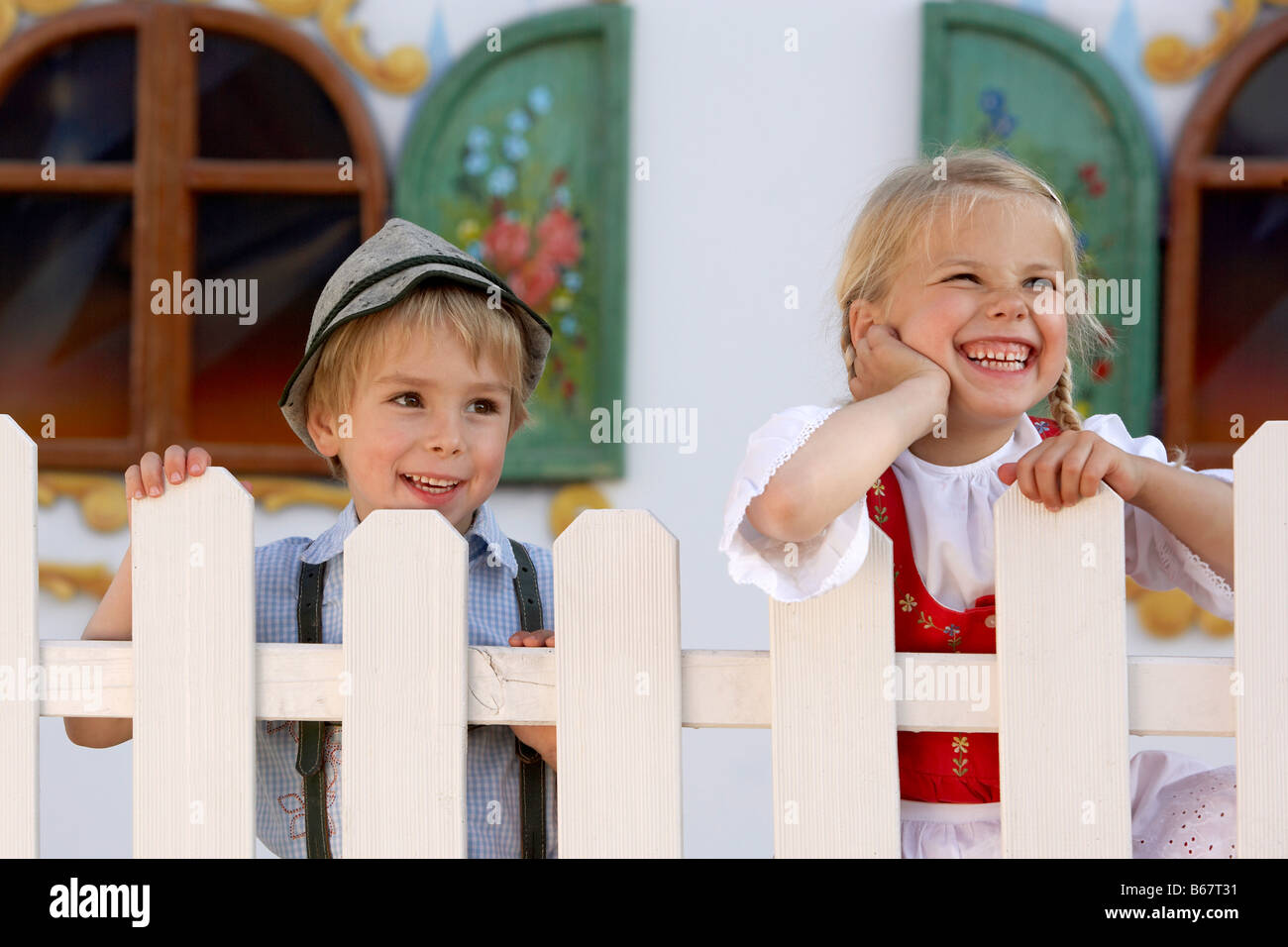 Two children (3-5 years) standing behind a fence - Stock Image