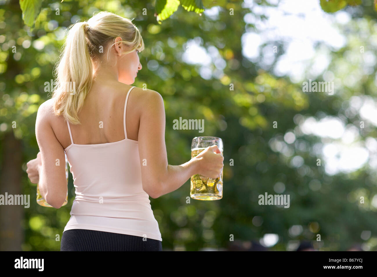 Young Woman In A Beer Garden Carrying Two Beer Steins Lake Stock
