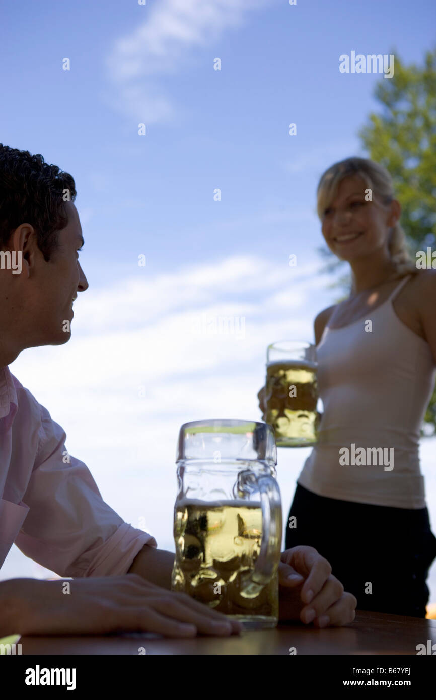 Two young adults meet in beergarden near Lake Starnberg, Bavaria, Germany - Stock Image