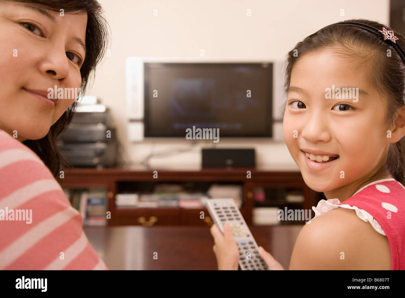 Portrait of a girl holding a remote control and smiling with her mother - Stock Image