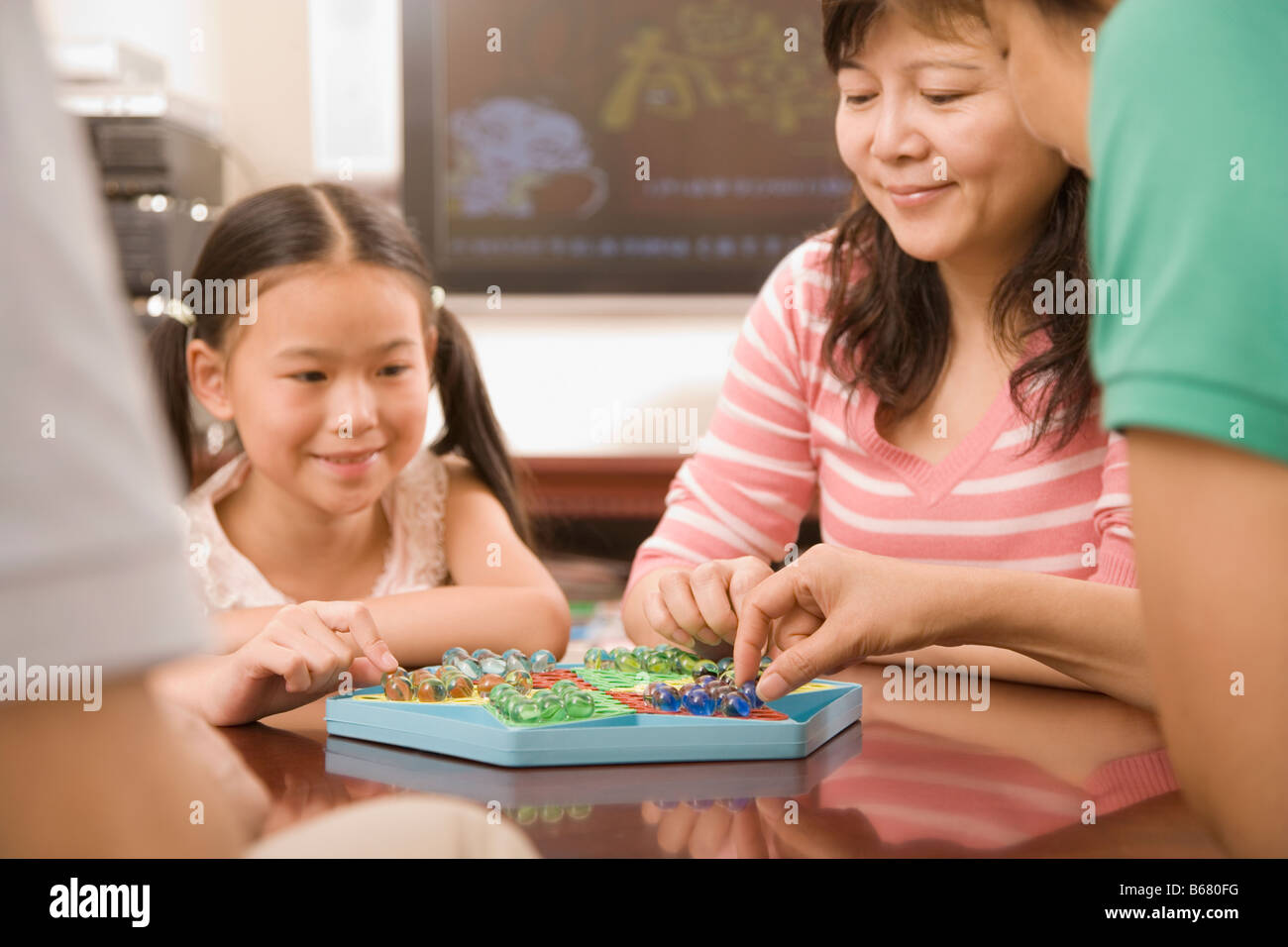Girl playing Chinese checkers with her mother - Stock Image