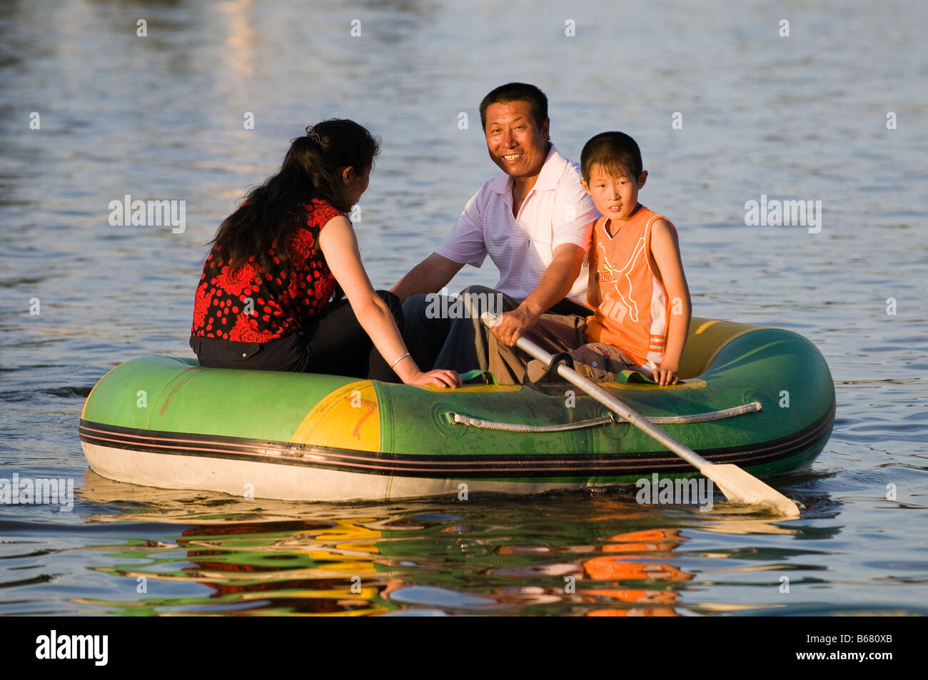 Mother and father with one child row boat in park Xiwuzhumuqinqi Inner Mongolia China - Stock Image