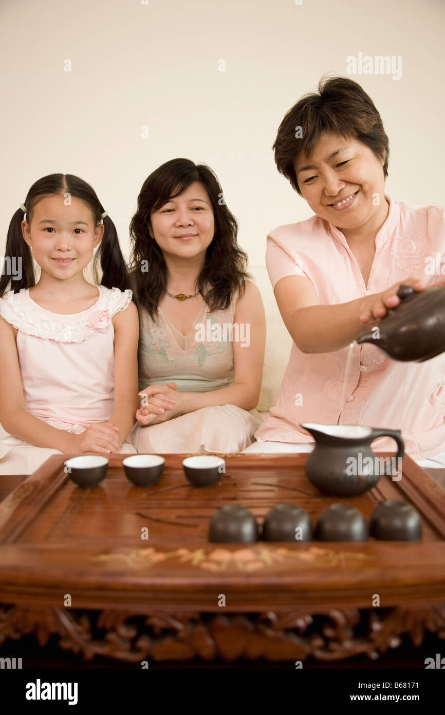 Mature woman pouring tea into a teapot with another mature woman and her daughter sitting beside her - Stock Image