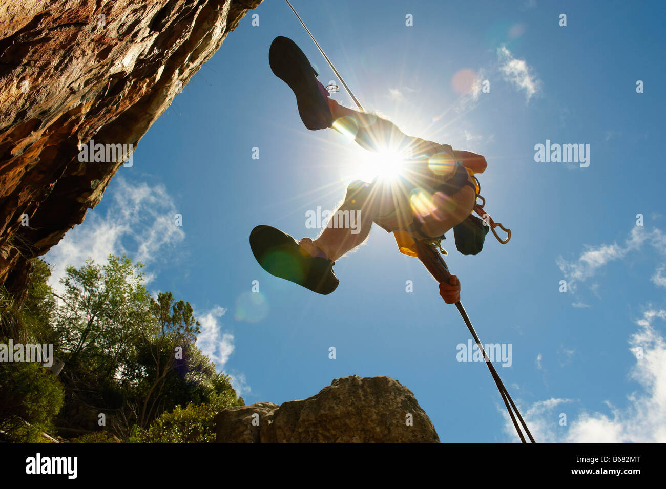 Man descending on abseil rope - Stock Image