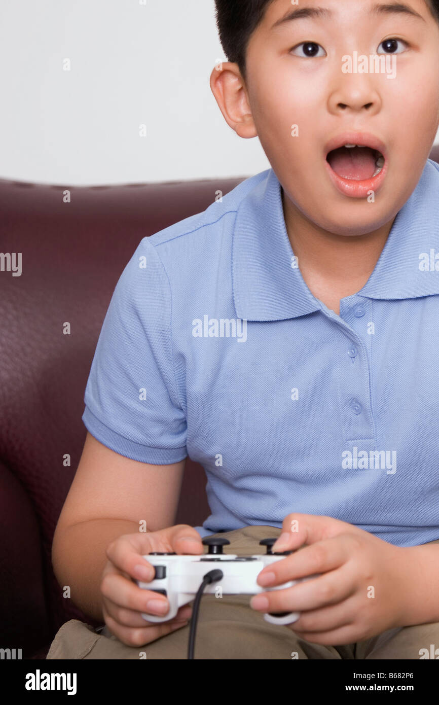 Close-up of a boy playing video game - Stock Image