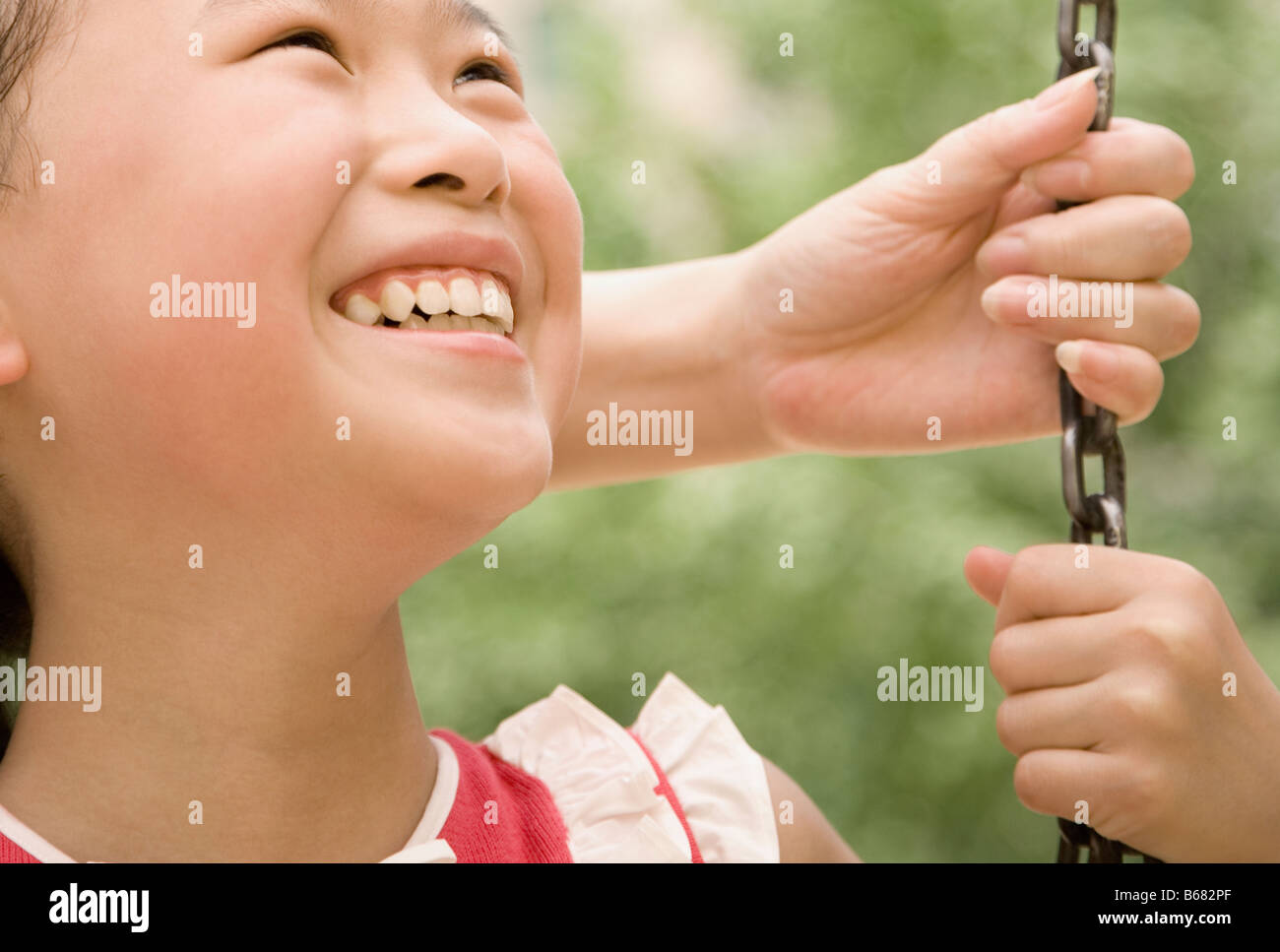 Close-up of a girl smiling on a swing - Stock Image
