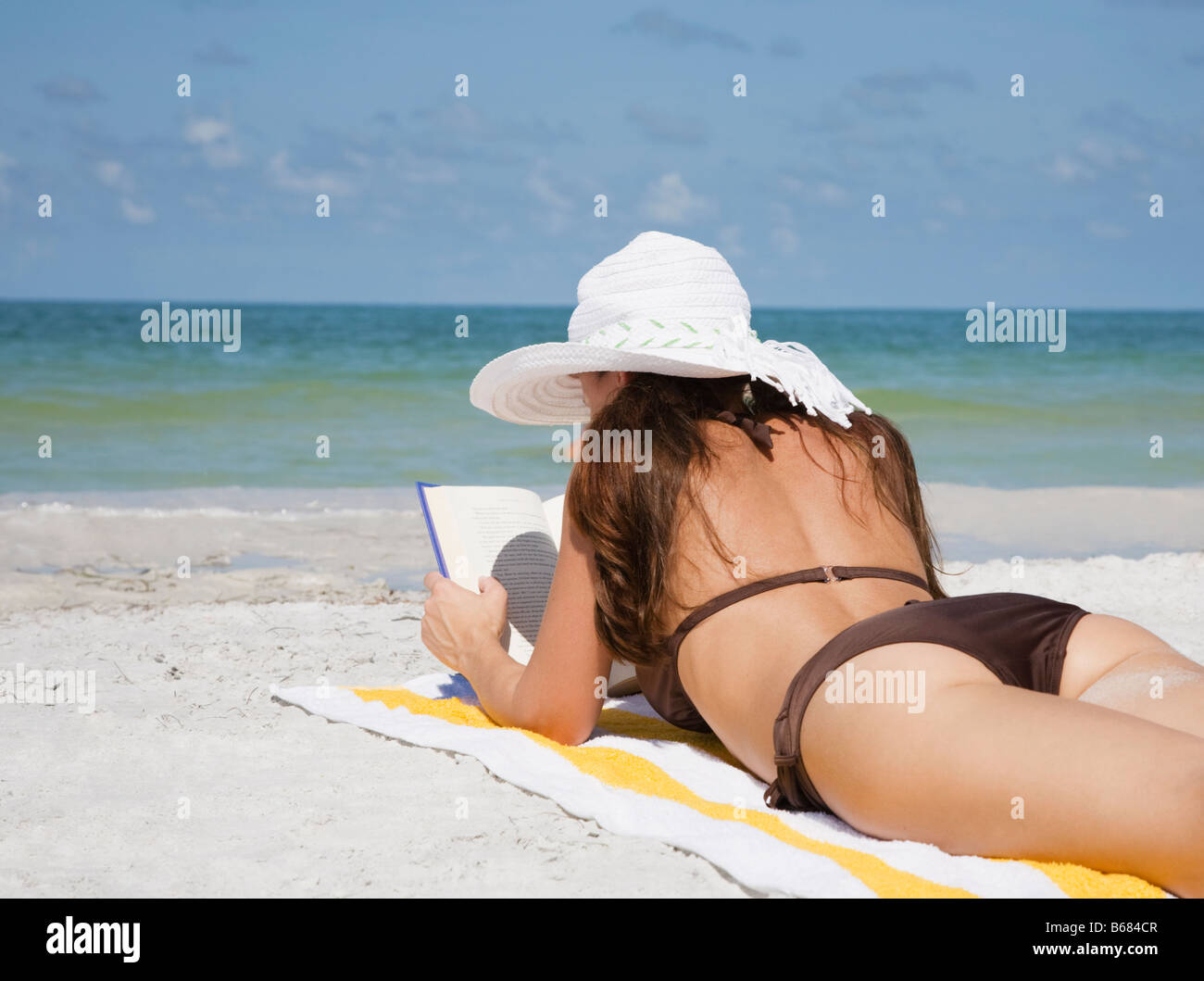 Woman reading book on beach - Stock Image