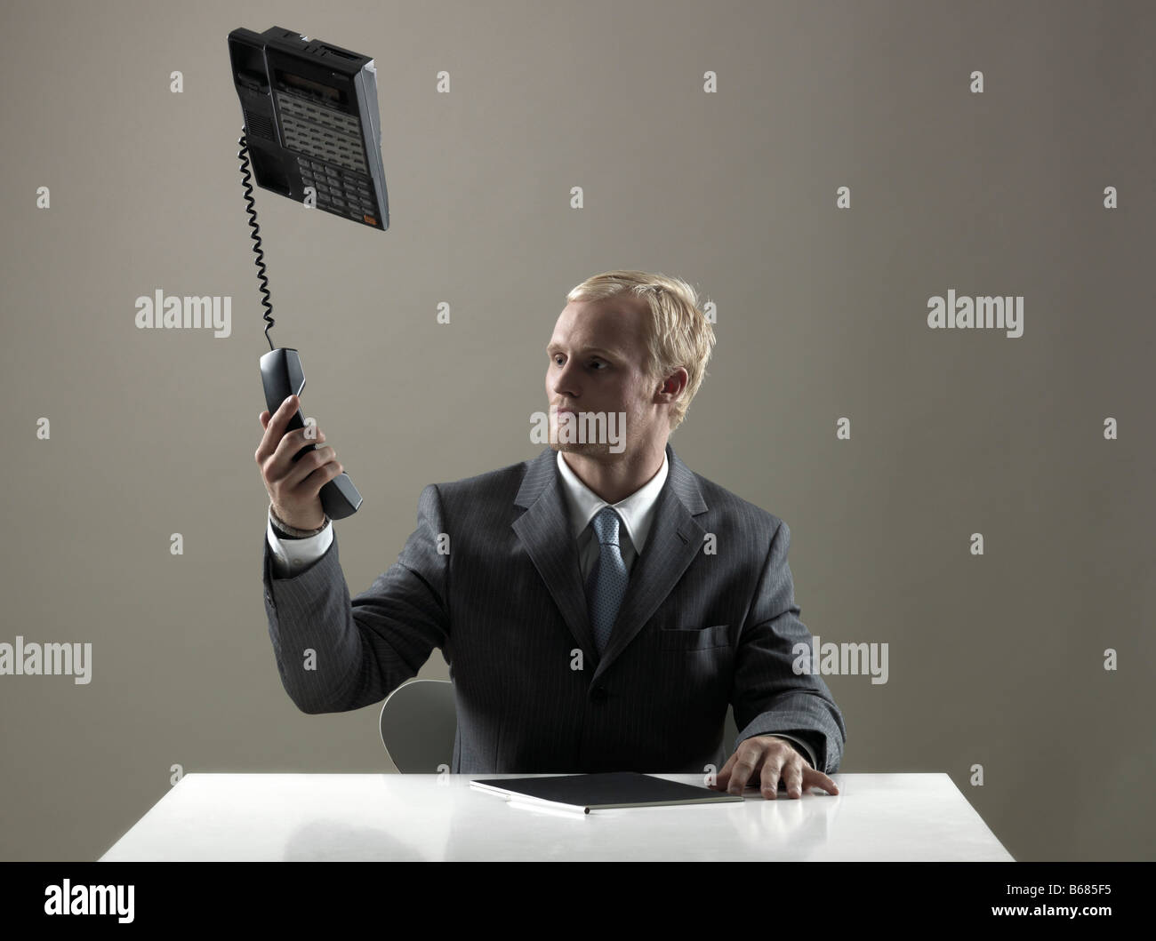 Business man holding phone in mid-air - Stock Image