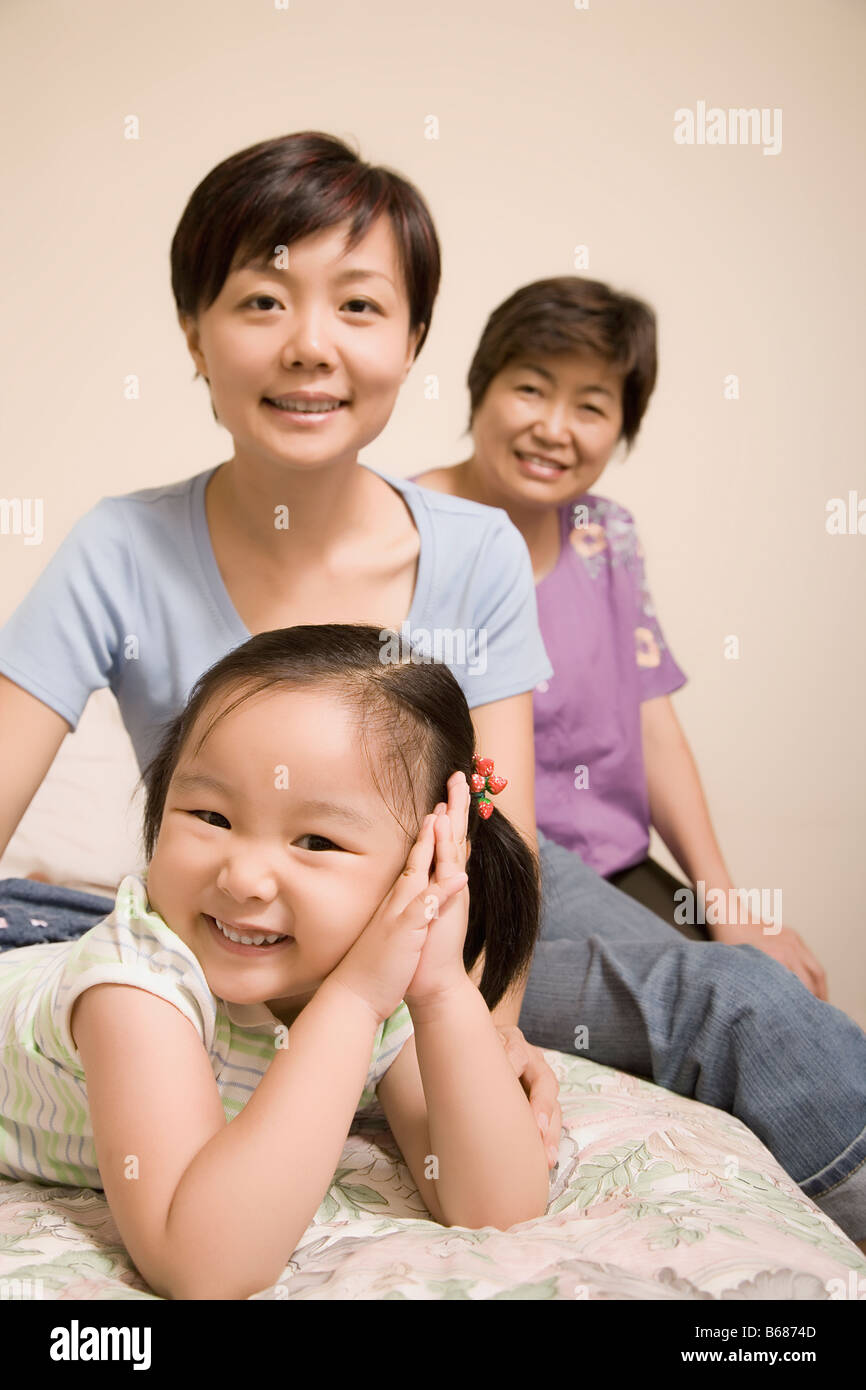 Portrait of a girl smiling with her mother and grandmother - Stock Image