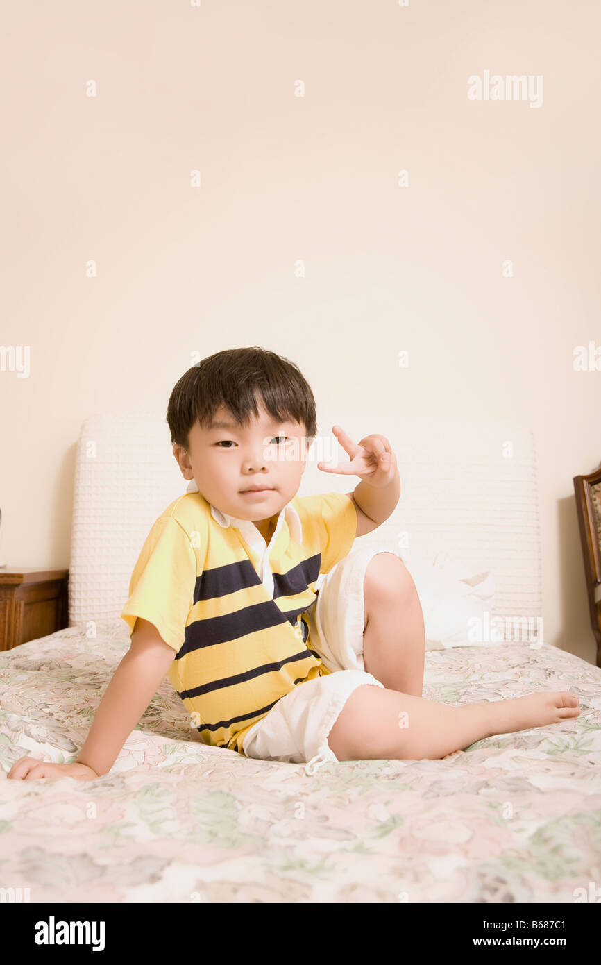 Portrait of a boy showing a peace sign and smiling - Stock Image