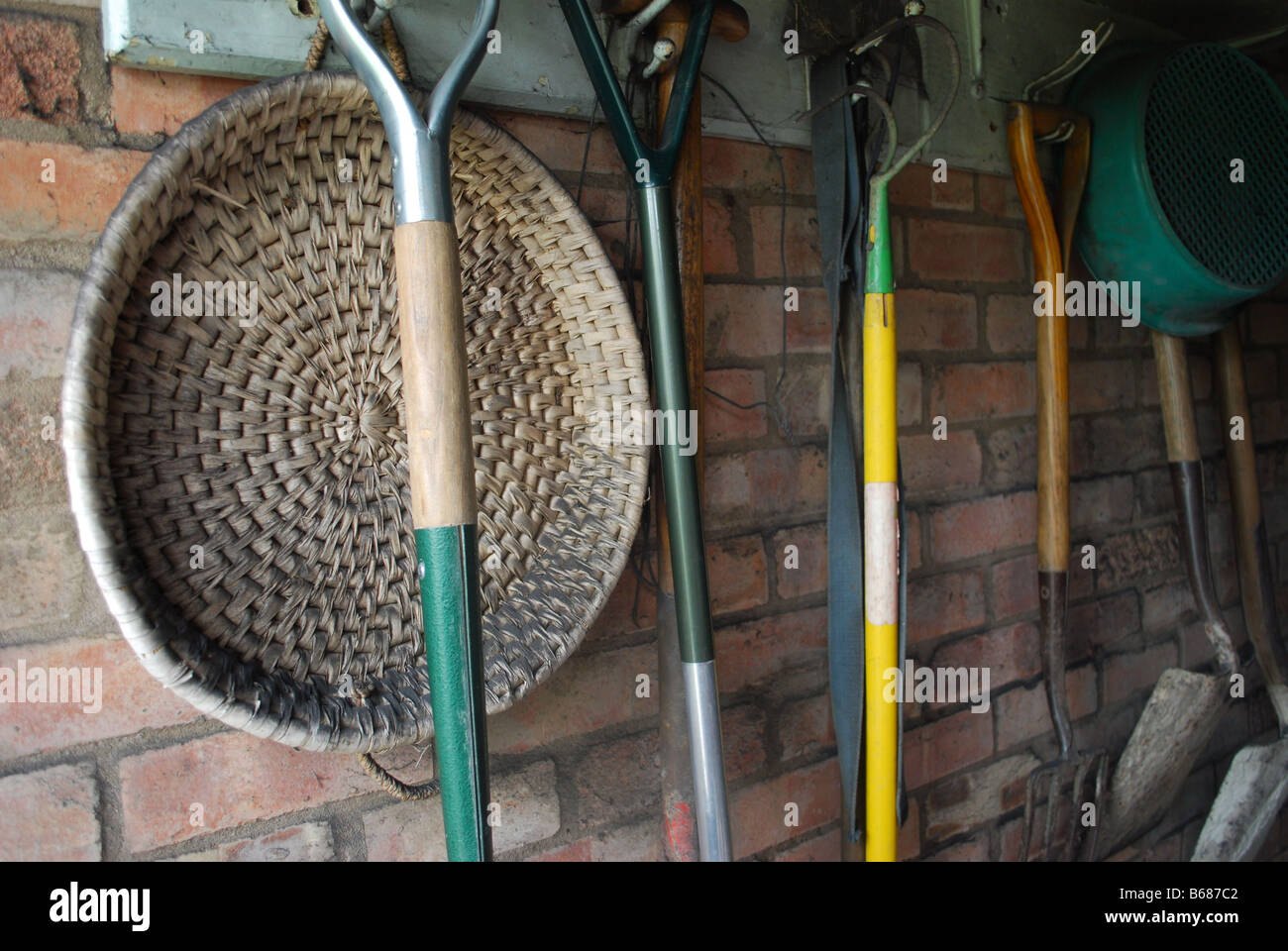 Flat Wicker Basket And Garden Tools Hanging From Hooks In A Brick Built  Shed