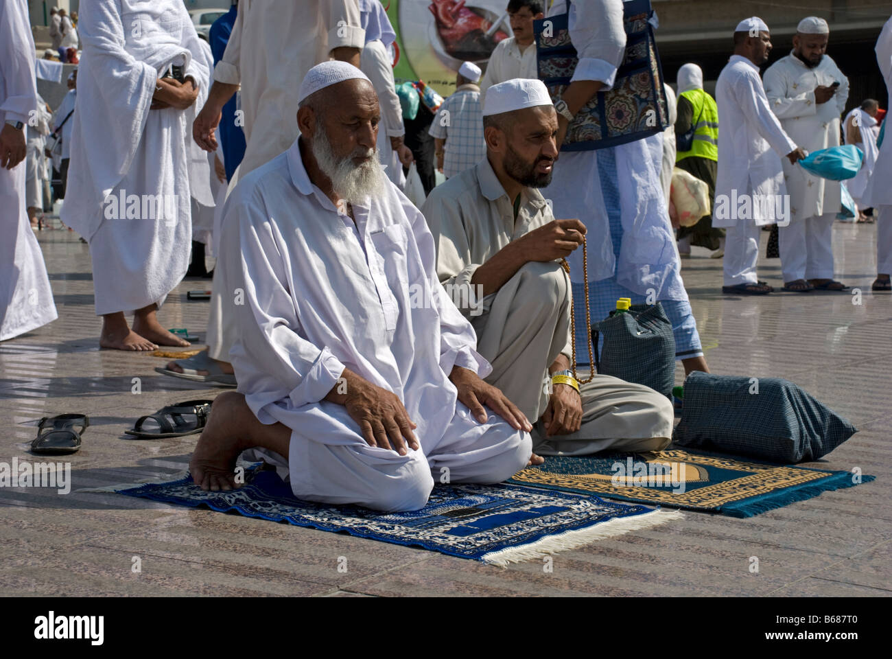 An Old And A Young Muslim Man Sitting On Their Prayer Rugs