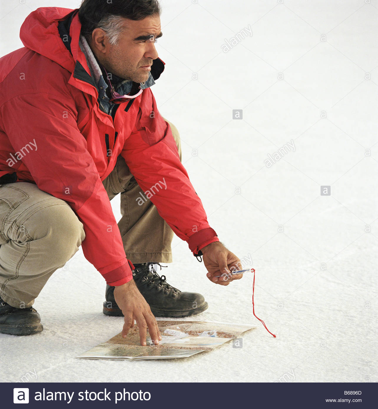 Man crouching in the desert with map - Stock Image