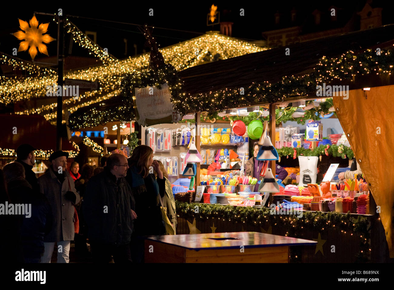 Light chains above stalls on a german christmas market - Stock Image