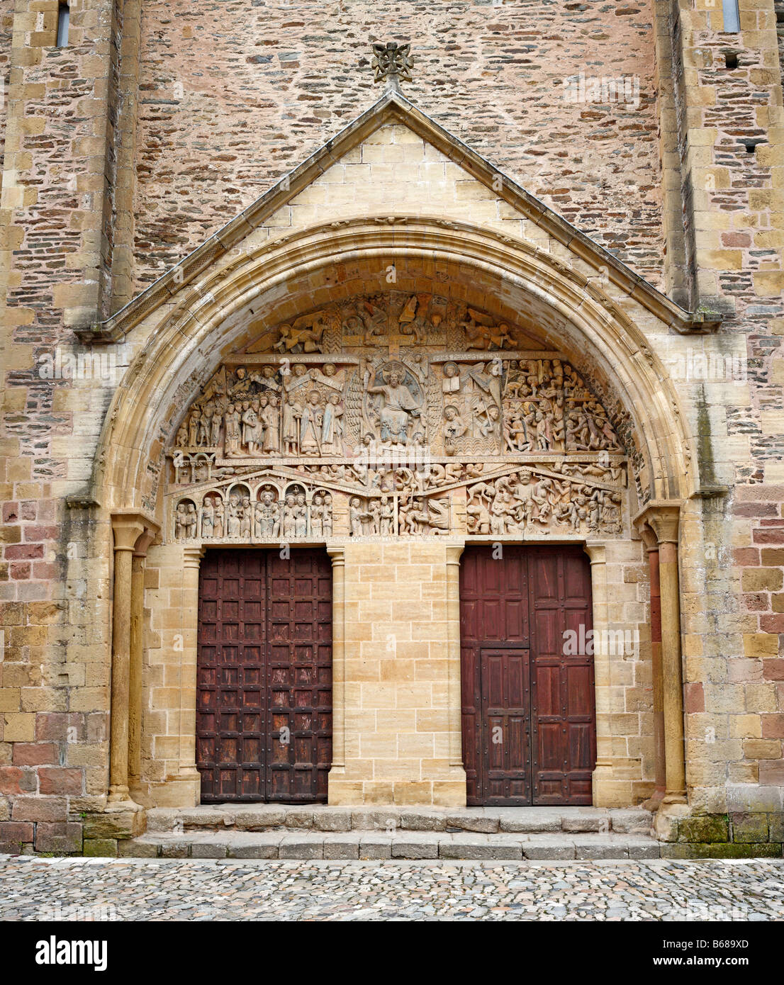 Romanesque sculpture, stone carved bas relief on portal of Sainte Foy abbey church (1124), Conques, France - Stock Image