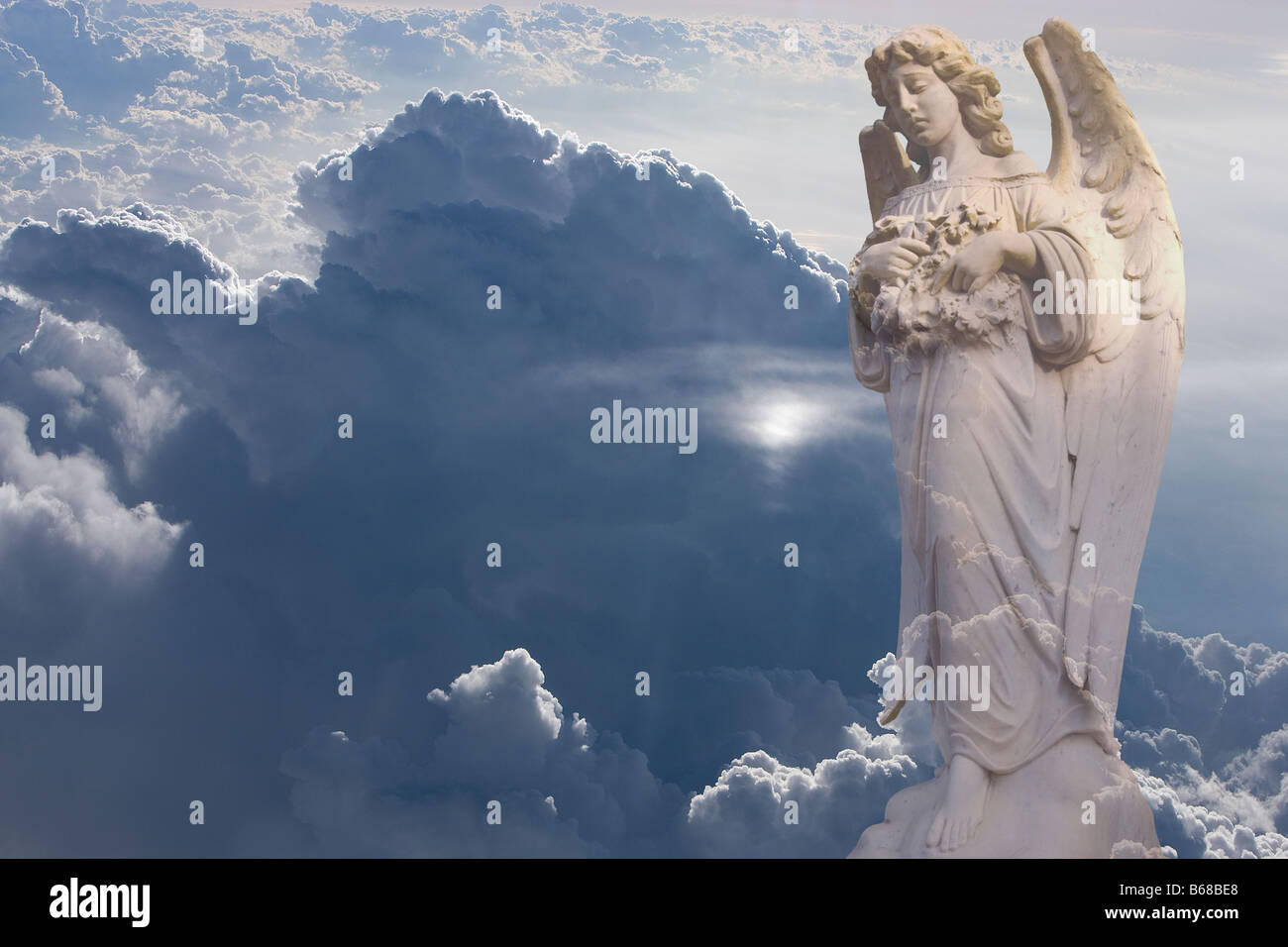 Statue of angel and aerial photo of clouds - Stock Image
