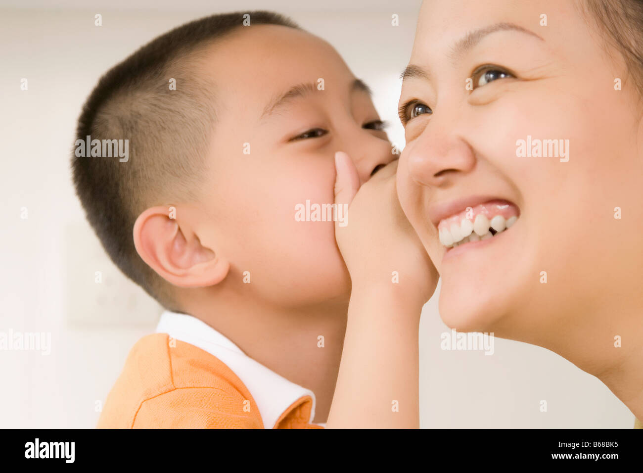 Close-up of a boy whispering to his mother - Stock Image