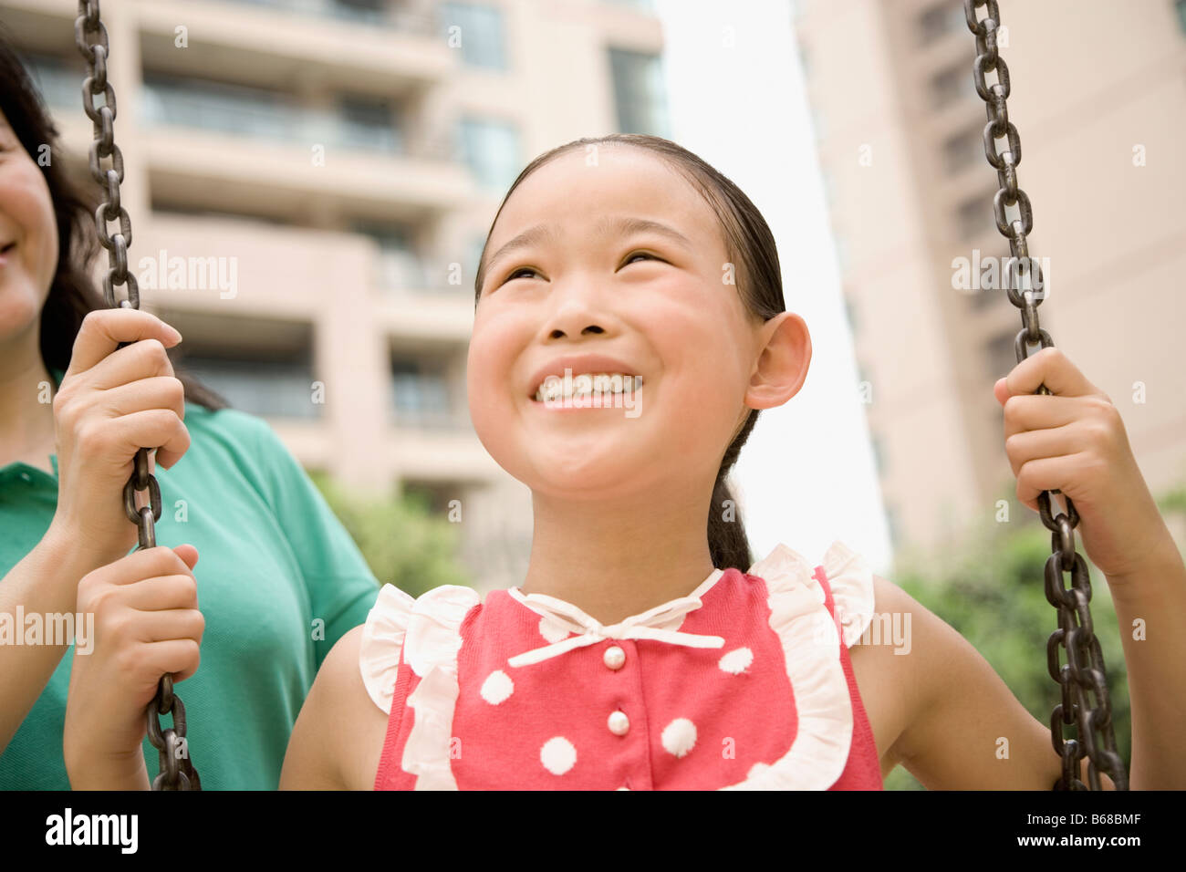 Close-up of a girl smiling on a swing with her mother behind her - Stock Image