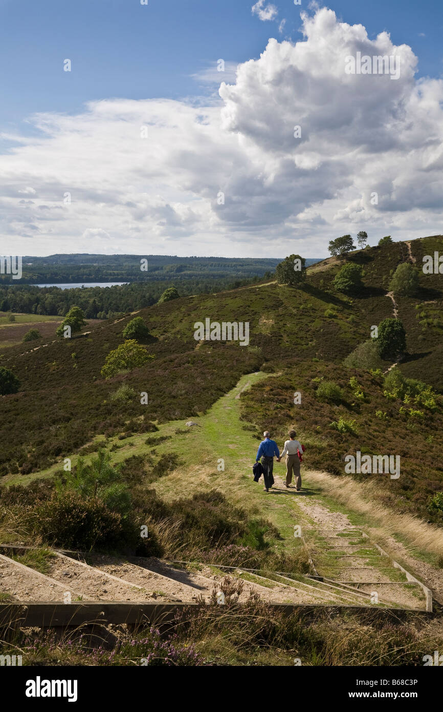 Couple walking on Stovbjerg hill and view to Sindbjerg hill and lake Brassø, near Sejs, Jutland, Denmark - Stock Image