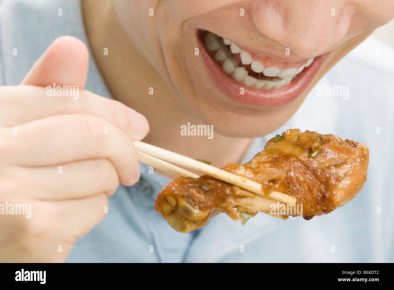 Close-up of a male office worker eating meat with chopsticks - Stock Image