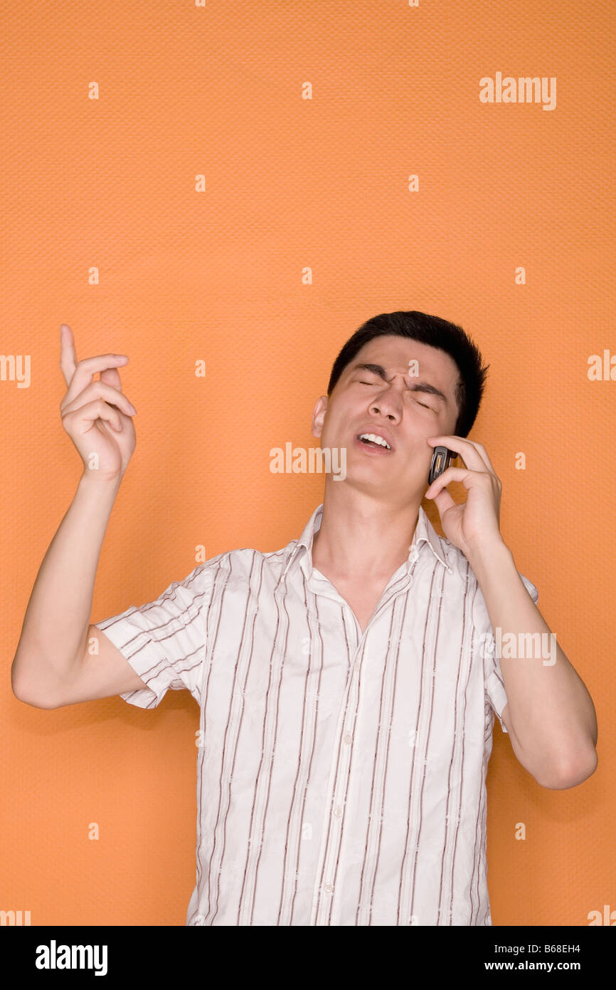 Male office worker talking on a mobile phone and looking shocked Stock Photo