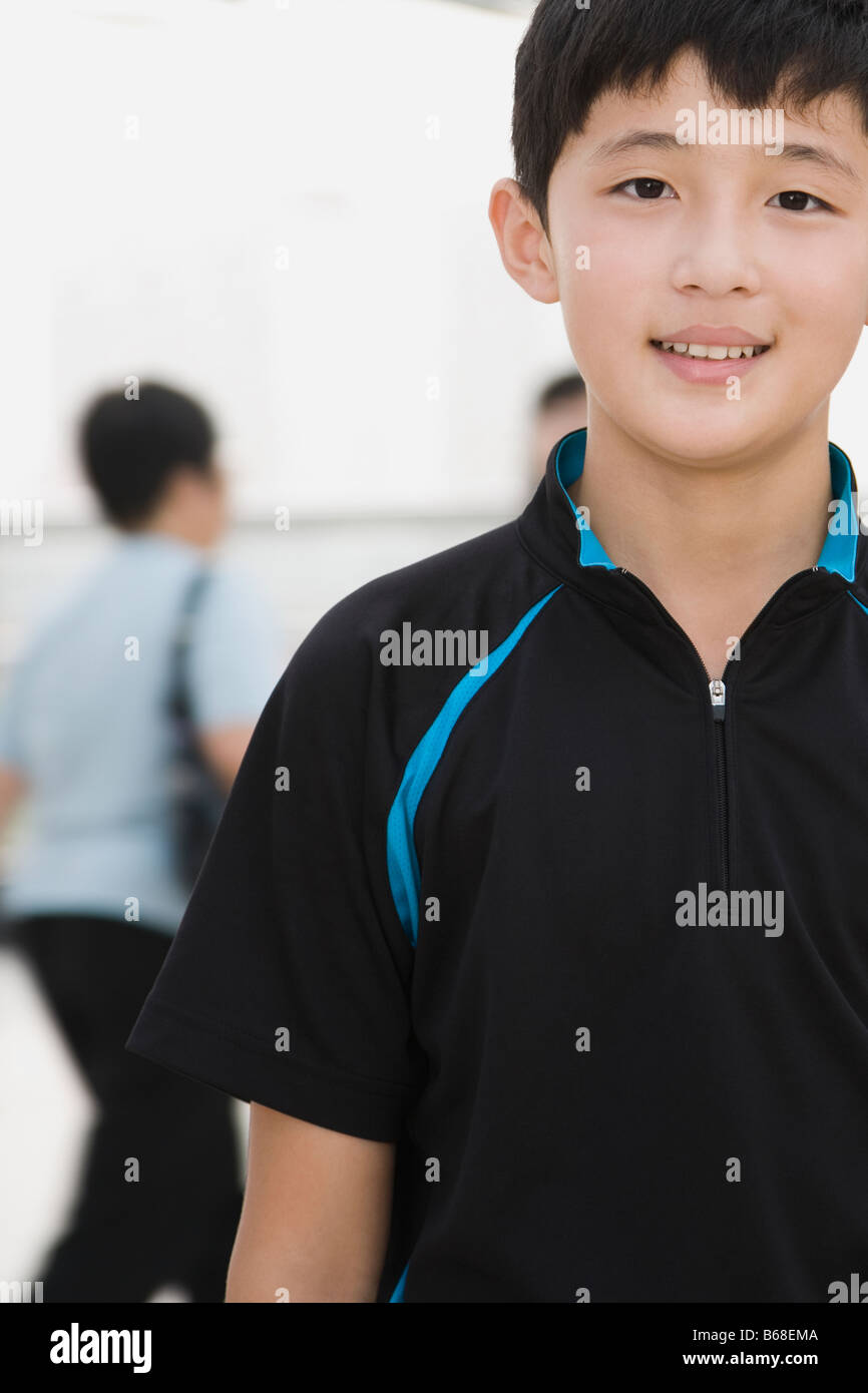 Portrait of a teenage boy standing in a corridor and smiling - Stock Image