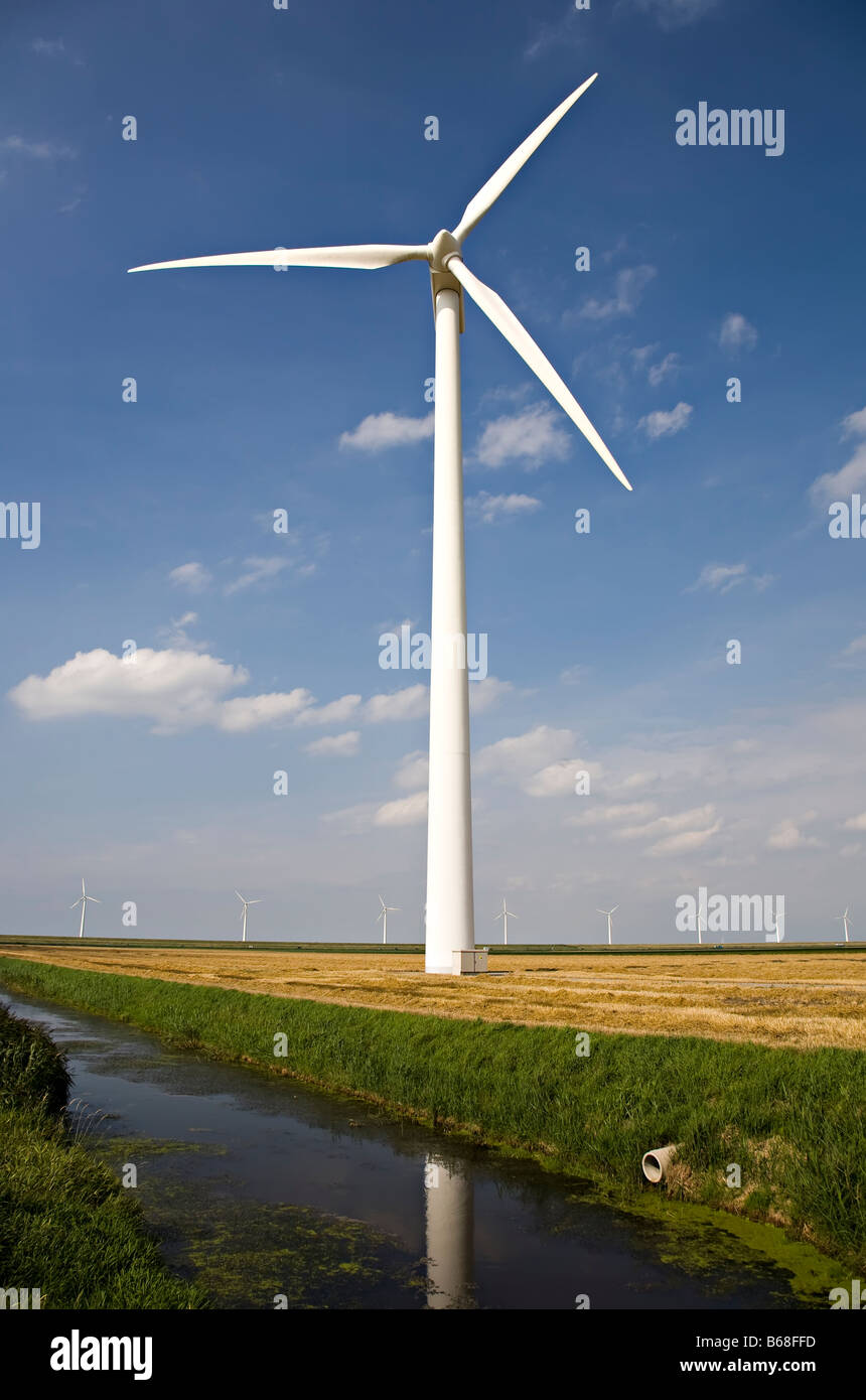 Wind turbine in field beside irrigation canal Netherlands - Stock Image