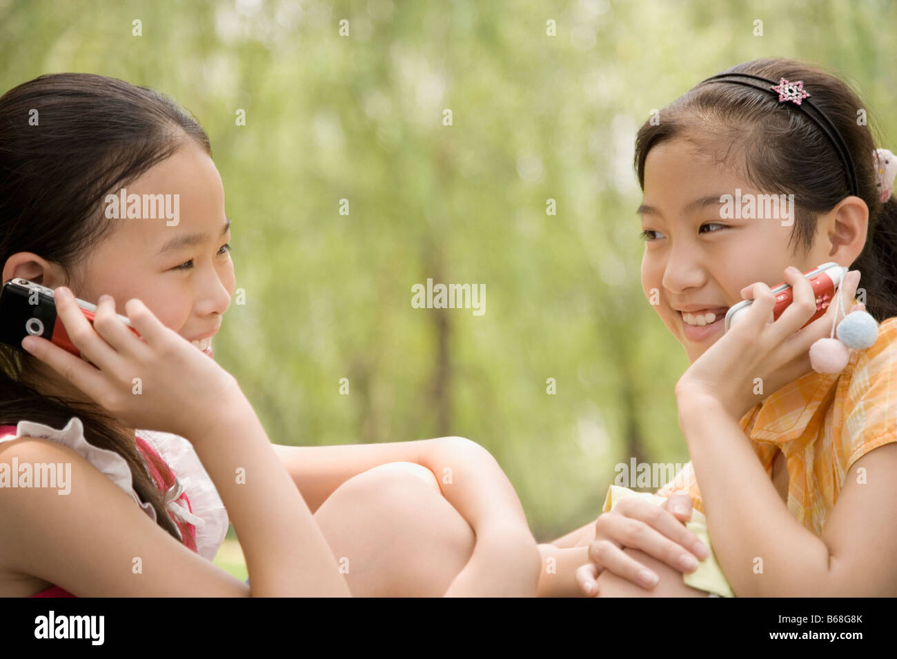 Two girls talking on their mobile phones and smiling Stock Photo