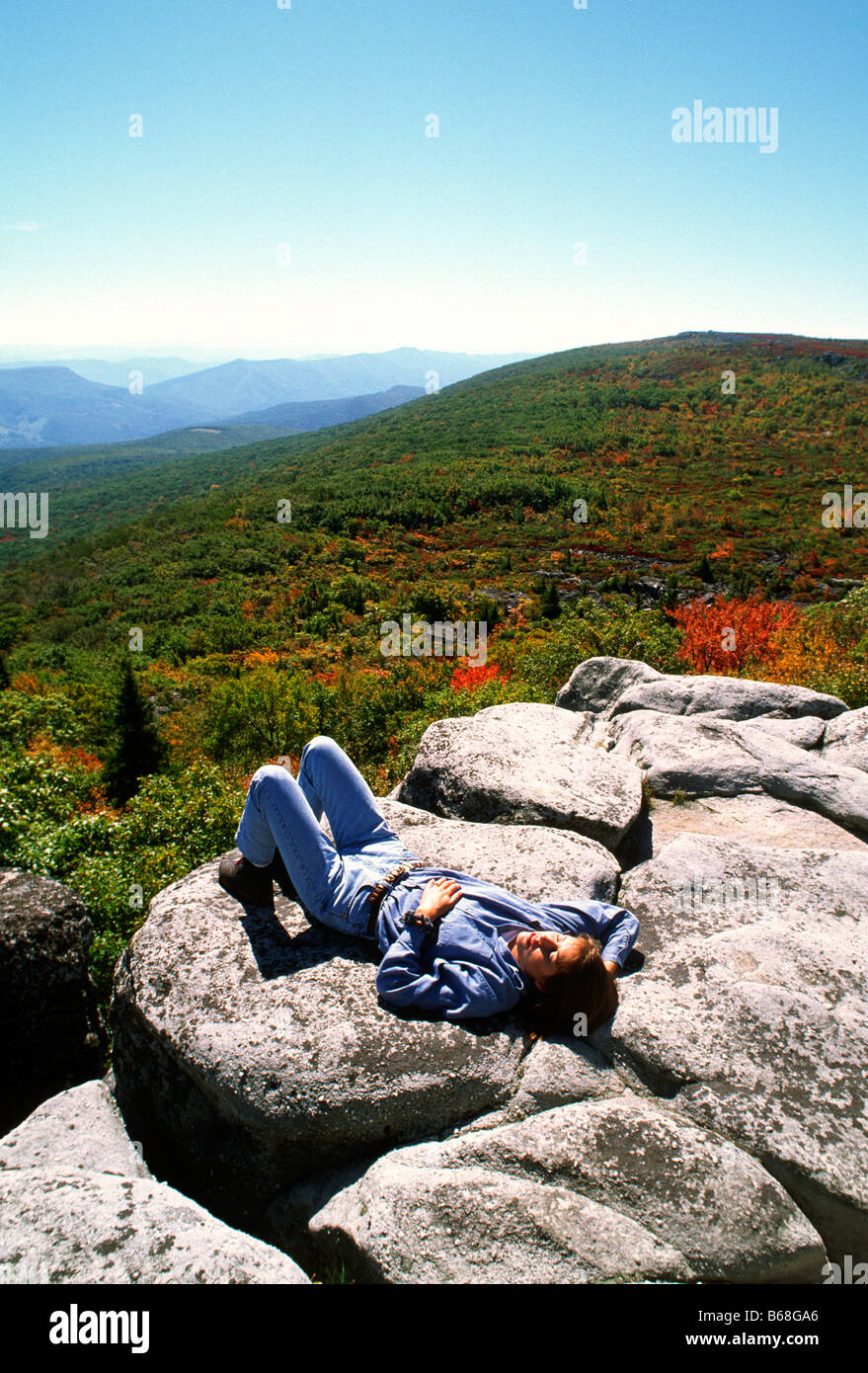 A woman enjoys resting in the sunshine on a mountain overlook Dolly Sods West Virginia - Stock Image