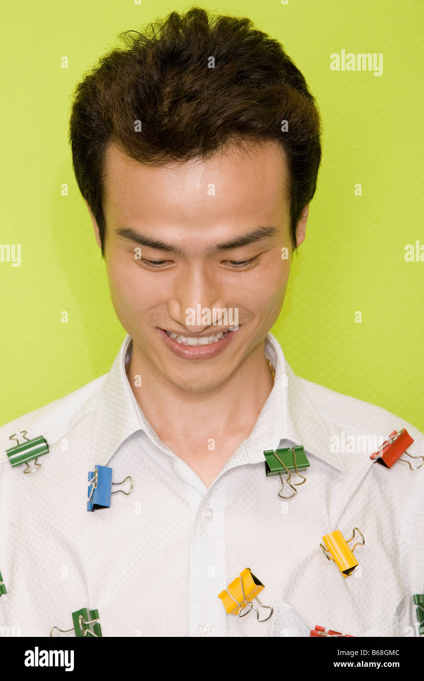 Close-up of a young man with paper clips on his shirt and smiling - Stock Image