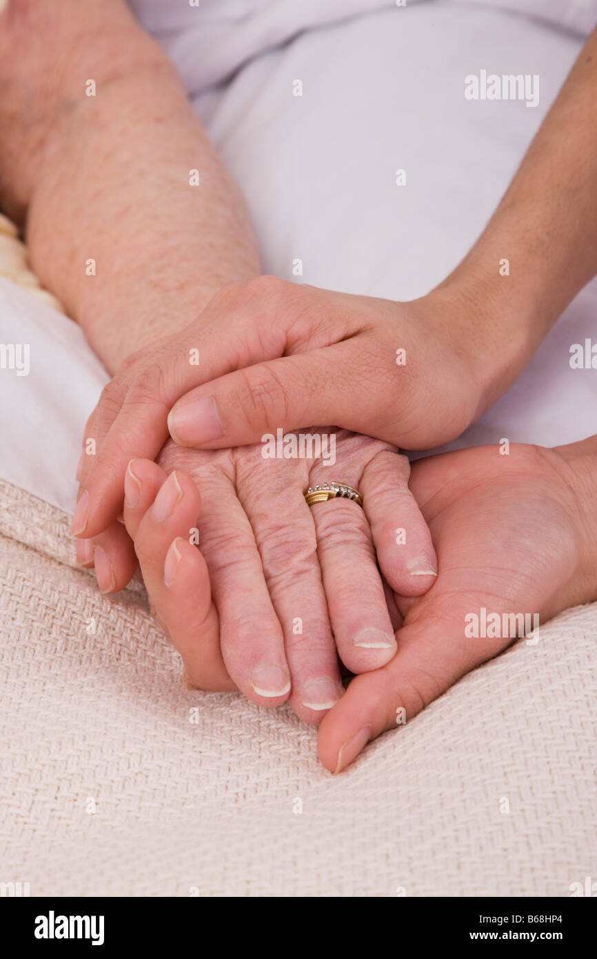 Woman holding senior woman's hand on bed, close-up - Stock Image