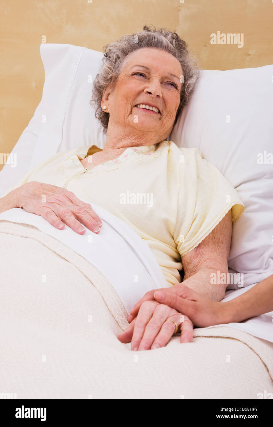 Woman holding senior woman's hand on bed - Stock Image