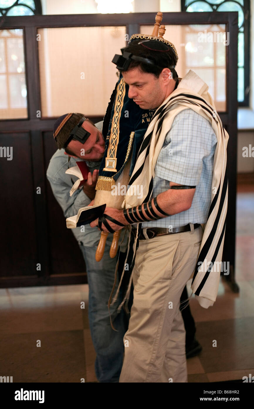 One man kisses the Torah as another carries it during services in the Nozyk Synagogue in Warsaw. Stock Photo