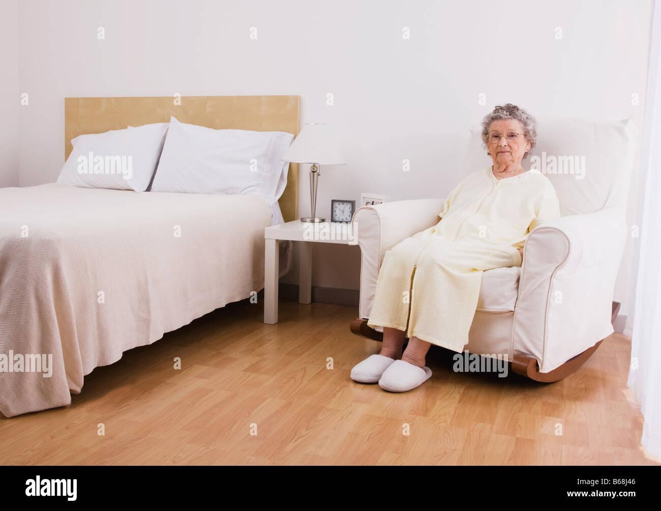 Senior woman sitting in armchair in bedroom - Stock Image