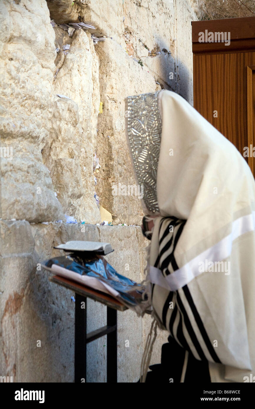 orthodox jew covered by a talis talit standing in front of and praying at the Western Wall in Jeruslalem Israel - Stock Image