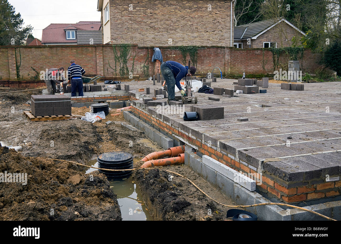 Workmen Laying Concrete Blocks To Build The First Stage Of A House Floor.