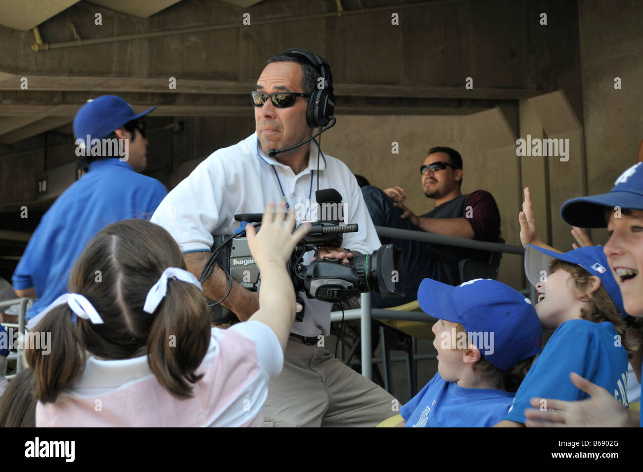 Video camera crew checks big screen while transmitting images of excited young baseball fans - Stock Image