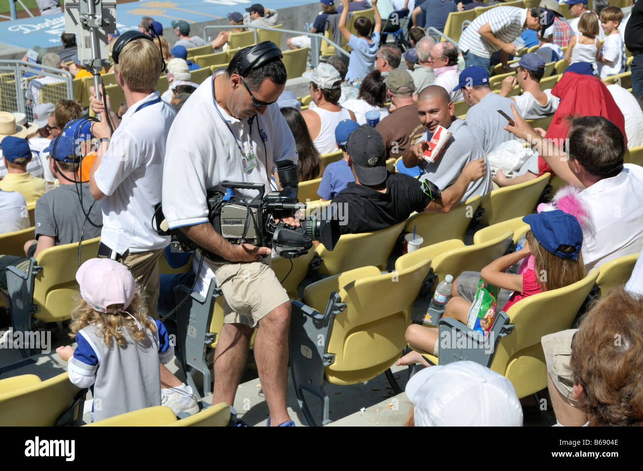 Video camera crew transmitting images of excited young baseball fans - Stock Image